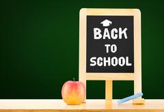 Back to school word on blackboard on wood table with apple,chalk at green bac Stock Photos