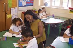 Female Elementary School Teacher Helping Pupils At Desk Stock Photos