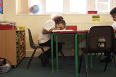 Female Pupil Working At Desk In Elementary School Classroom Kuvituskuvat