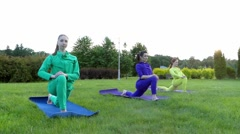 Yoga in the Park. Three Girls in Sport Wear Stretched Legs. Stock Footage