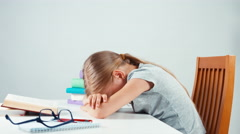 Sad schoolgirl 7-8 years does not want read a book and homework Stock Footage