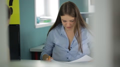 Brunette attentively looks through various kinds of documents in office Stock Footage