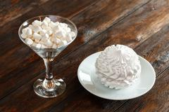 Glass with white fluffy marshmallows and zephyr, wooden background Stock Photos