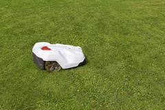 Robotic lawn mower working on green grass Stock Photos