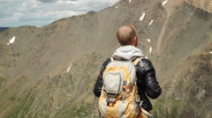 Hiker with backpack standing on top of a mountain - stock footage