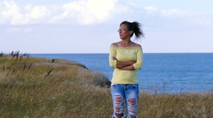4K. Adult woman in yellow blouse  stand against sea surface in windy day Stock Footage