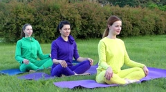 Yoga Class in the Park. Three Gils Sitting in the Lotos Pose and Turn Body. Stock Footage