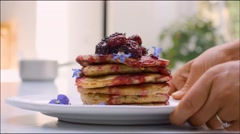 Stacked Pancakes with rapsberry compote and edible flowers Stock Footage