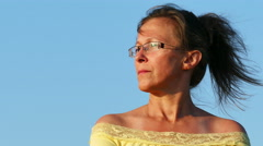 4K.Face of  adult woman in yellow blouse   against blue sky Stock Footage