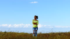 4K. Adult woman in yellow blouse  stand in grass against  blue sky Stock Footage