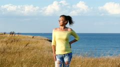 4K. Adult woman in yellow blouse  stand  on seashore. Focus change Stock Footage