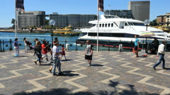 Australia Sydney People walking by water as an excursion boat pulls out Stock Footage
