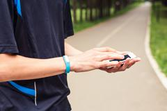Man use mobile phone sync with activity tracker - stock photo