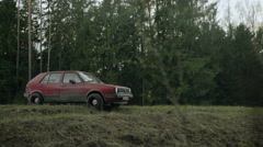 Abandoned old car on the forest road - stock footage