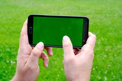 Man holding smart phone in hands against green spring background. - stock photo