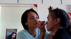 Gay beautician applies eye liner to a girl Stock Footage