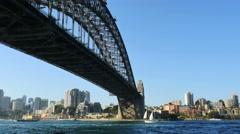 Australia Sydney sailboat moves under Harbour Bridge Stock Footage
