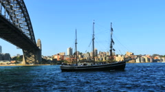 Australia Sydney traditional ship sails by Harbour Bridge Stock Footage