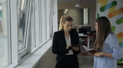 Two women stand in corridor near windows and discuss plans for today Stock Footage
