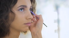Professional makeup artist applying make up on a beautiful young face for a Stock Footage