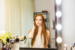 Head and Shoulders of Attractive Young Woman with Red Hair Admiring Reflection - stock photo