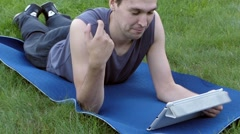 A Young and Handsome Guy is Lying on the Mat in the Park and Looks at the Stock Footage