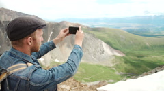 Strong man hiker taking photo with smart phone at mountain peak. Marvelous Stock Footage