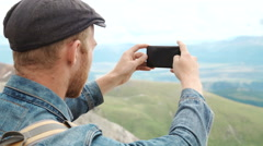 Tourist takes photos with smart phone on peak of rock Stock Footage