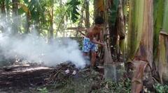 Young man burning backyard rubbish Stock Footage