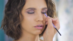 Professional makeup artist applying make up on a beautiful young blond model Stock Footage