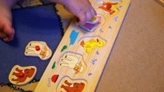 The child assembles a puzzle with animals Stock Footage
