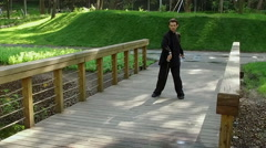Training in the park. Man practicing elements of tai chi. Slow motion. HD Stock Footage