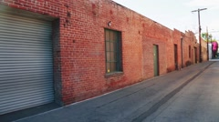 Establishing shot of rustic building and garage on an alley - stock footage