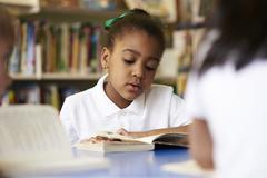 Female Elementary School Pupil Reading In Library Stock Photos