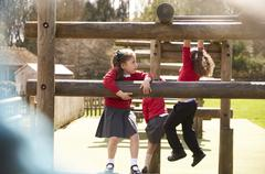 Elementary School Pupils Play On Climbing Frame At Breaktime Stock Photos