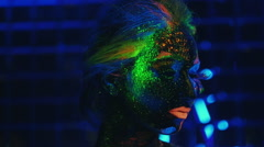 Young girl painted fluorescent powder , laughing in ultraviolet light Stock Footage