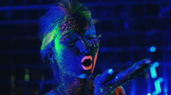 Girl painted fluorescent powder blows with the palm green powder Stock Footage
