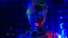 Girl in ultraviolet light blows green fluorescent powder with palm Stock Footage