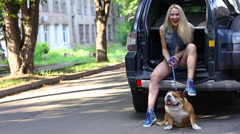 Beautiful female smilling style portrait sitting car american bulldog Stock Footage