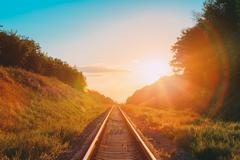 Railway Going Straight Ahead Through Summer Hilly Meadow To Suns Stock Photos