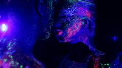Passion couple in love painted fluorescent powder under ultraviolet light. Stock Footage