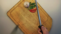Male hands sharpening a knife against a background of an old wooden cooking - stock footage