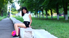 Young beautiful Asian girl uses phone, calls and talks in the green park Stock Footage