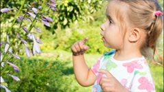 Girl playing with a flower and looking at the camera. large eyes of a child Stock Footage