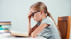 Portrait profile sad student girl 7-8 years old reading book Stock Footage
