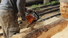 Man cuts off beam chainsaw for future home. Construction works with a wooden Stock Footage
