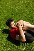 Urban athlete doing stretching exercises on the grass Stock Photos