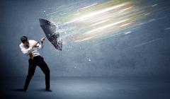 Business man defending light beams with umbrella concept - stock photo