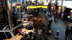 People visit departure hall in international Schiphol airport - stock footage