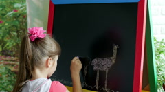 Little girl draws on easel - timelapse Stock Footage